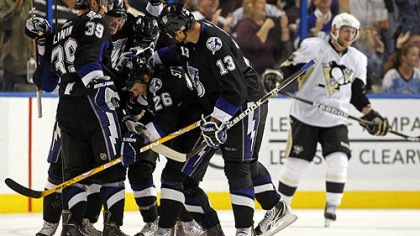 Lightning forward Martin St. Louis, No. 26, is congratulated on his goal by teammates, including, from left, Mike Lundin, No. 39, Steven Stamkos, No. 91, and Pavel Kubina, No. 31 as Penguins forward Matt Cooke skates in the background during the third period Wednesday's game at the St. Pete Times Forum in Tampa, Fla.