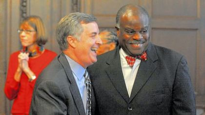 Pittsburgh Public Schools Superintendent Mark Roosevelt, left, shares a laugh with school board  member Mark Bentley Sr., after announcing his resignation.