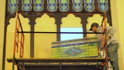 Bryant Raymond of Sarver installs a stained-glass window Tuesday at the Union Project in Highland Park. Since 2004, the Union Project has been restoring and reinstalling 153 neo-gothic style stained-glass windows throughout the former church building.