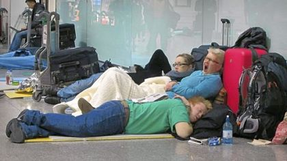 Passengers sleep on the floor as they wait for flights from Terminal 3 at Heathrow Airport in London on Tuesday. Heathrow, one of the world?s busiest airports, planned to operate with only one runway for a third day as snow continued to cause travel delays. Full service was not expected until Thursday.