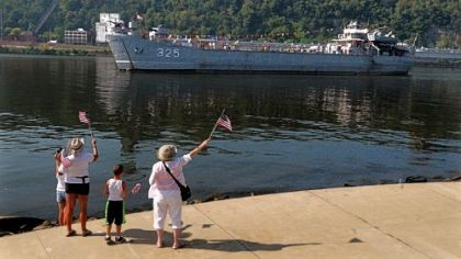 People wave flags for the LST 325 as it heads toward the North Shore of Pittsburgh.