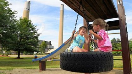Madi Kiddey, 5, and her sister Abi, 2, play in Shippingport Community Park across the street from the Bruce Mansfield power plant in Shippingport.