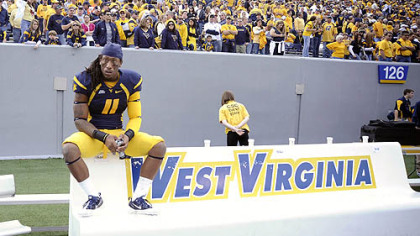 West Virginia&#039;s Bruce Irvin sits alone on the bench following a 19-14 loss against Syracuse Saturday in Morgantown, W.Va.