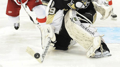 Penguins goaltender Marc-Andre Fleury steers a puck away from Red Wings forward Dan Cleary.