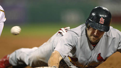 The ball gets away from Pirates first baseman Garrett Jones as the Cardinals' Skip Schumaker dives back to first on a pickoff attempt by  pitcher Charlie Morton in the second inning.