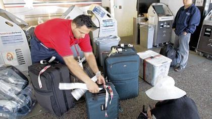 An American Airlines luggage handler helps passengers check in luggage Friday at San Jose International Airport. American Airlines said it planned to charge passengers $15 for the first checked bag.