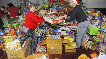 Jackie Curtis of Pitcairn hands Randy Winslow of Penn Hills a toy as volunteers from CVS Caremark help sort toys for Toys for Tots at Guardian Storage Solutions in the Strip District.