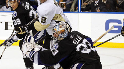 Lightning goaltender Dan Ellis,  makes a third-period save in front of teammate Mike Lundin and Penguins forward Pascal Dupuis.
