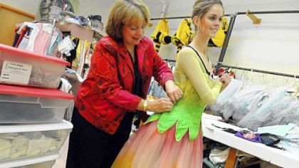 Janet Groom-Campbell, a costumier of the Pittsburgh Ballet Theatre, helps fit a costume on Danielle Downey.