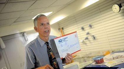 "Mike Herr holds up a sign that reads ""Nice Sneakers"" to the next person in line at the University Park post office."