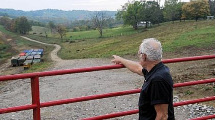 Taylorstown resident Thomas Westfall points to a pipeline buried under a strip of farmland.