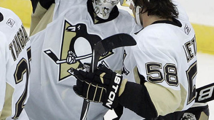 Penguins goaltender Brent Johnson is congratulated by defenseman Kris Letang after the Penguins defeated the Devils 3-1.
