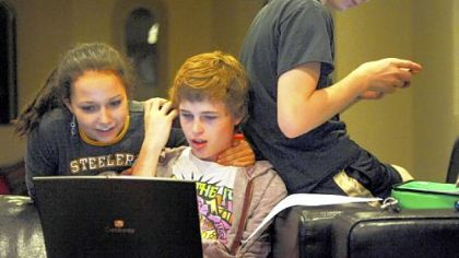 Elizabeth Truell, 15, looks over Cameron Clark's shoulder while he's on his computer as Seth Klein-Tooley, 13, of Spokane, Washington, checks his phone at the Pittsburgh Ballet Theatre's Byham house for out-of-town students.
