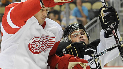 Penguins forward Mike Comrie battles Red Wings forward Jonathan Ericsson.
