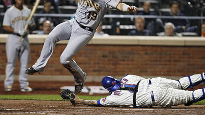 The Pirates' Chris Snyder leaps to avoid being tagged out at the plate by Mets catcher Henry Blanco on an RBI single by Andrew McCutchen during the fourth inning of tonight's game at Citi Field in New York. Snyder missed the plate in his leap and was forced to dive back, but Blanco dropped the ball on the play, allowing the run to score.