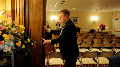 Matt Schellhaas, supervisor of Schellhaas Funeral Home in Bakerstown,pushes back the dividers to open the chapel area as he gets ready for a funeral service Thursday morning.