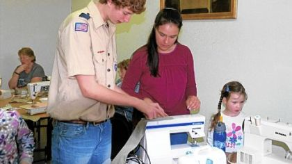 Noah Pillion-Gardner teaches Bonnie and Josie Dougherty how to make Cool Ties. The ties, which soldiers wear around their necks to beat the heat, are Noah's Eagle Scout project.