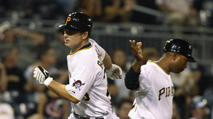 The Pirates' John Bowker, left, is greeted by third base coach Tony Beasley after hitting a solo home run in the second inning.