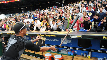 Pedro Alvarez flips a bat to the top of the Pirates&#039; dugout for a fan after the game Sunday. Several players tossed equipment and signed autographs.