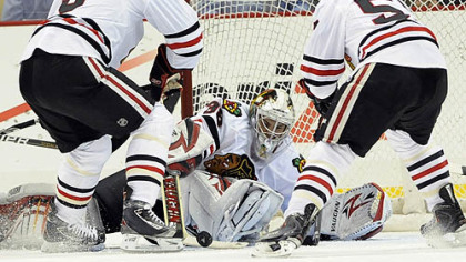 Blackhawks goaltender Alec Richards makes a save as defenseman Jassen Cullimore, left, and forward Ben Smith look to clear the puck during the first period.
