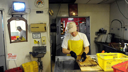 Aaron Mathers scales and fillets fish at his family's shop, The Last Fisherman, in Erie.